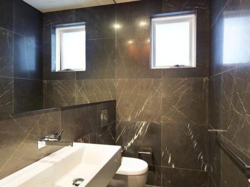 baño con pared de mármol gris